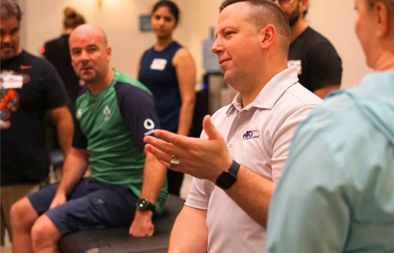 Male instructor discusses ART with attendees at a seminar.