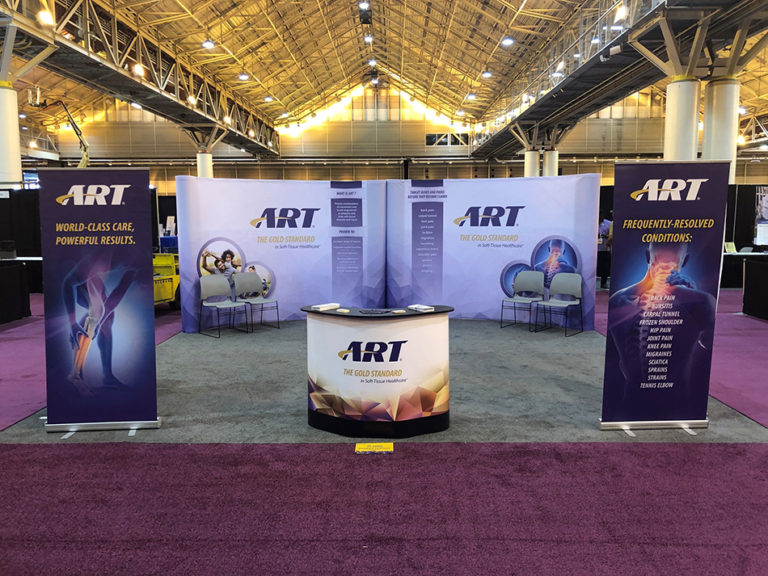 ART branded trade show set up. Includes chairs, backdrops, and an ART branded table.