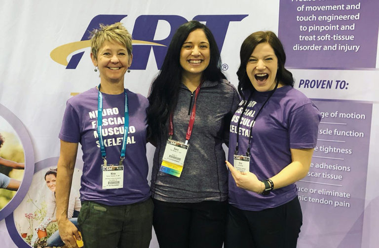 3 female booth visitors pose in front of and ART branded backdrop at a trade show.