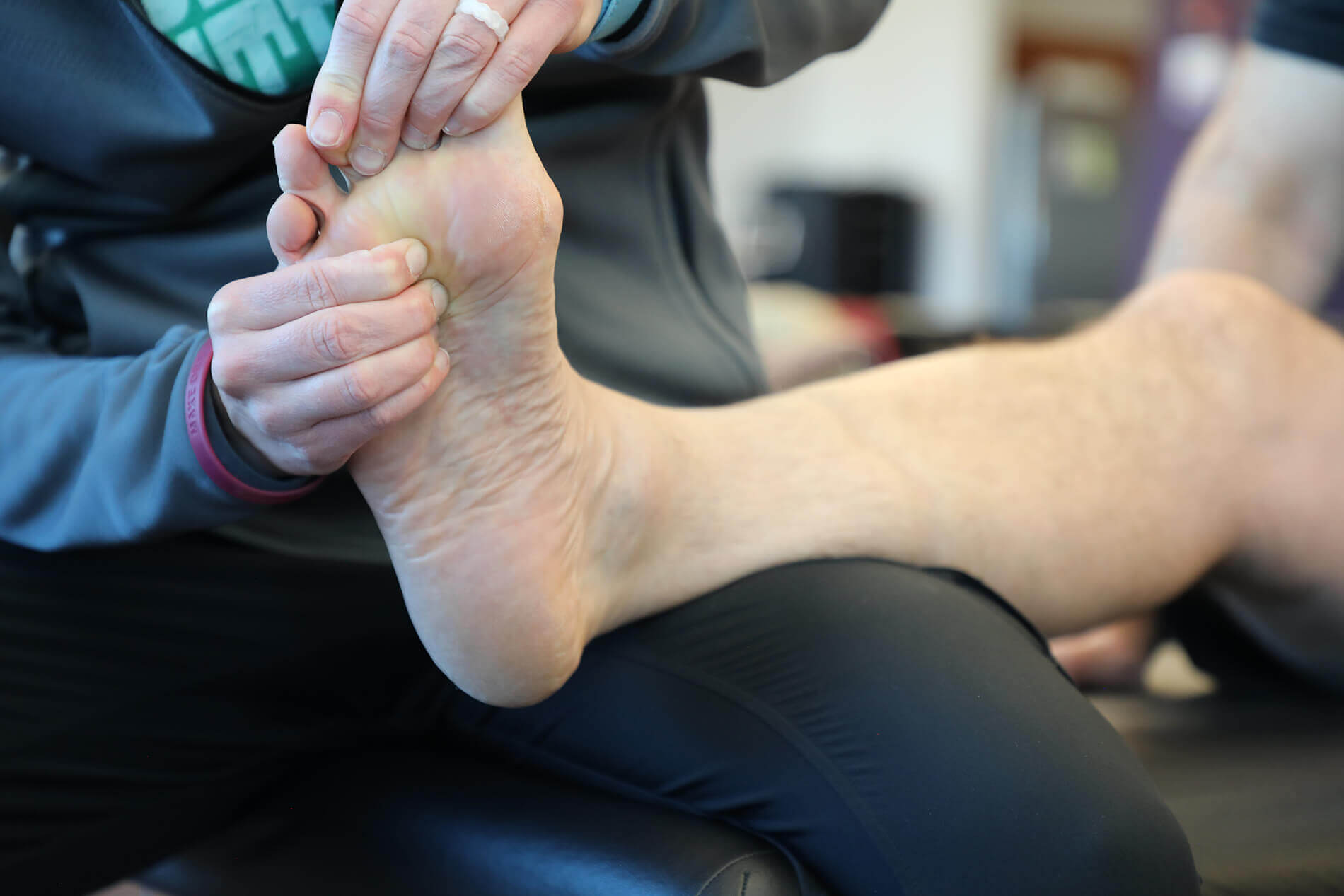 Image of a foot with a seminar attendee practicing Lower Extremity techniques on it.